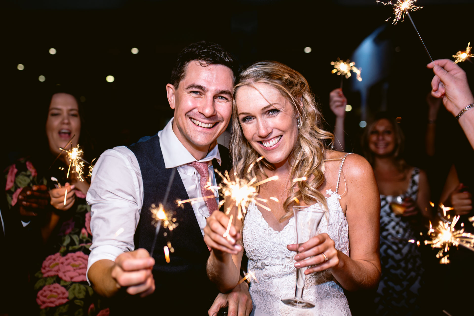 bride and groom standing and holding sparkles in salcombe harbour hotel wedding