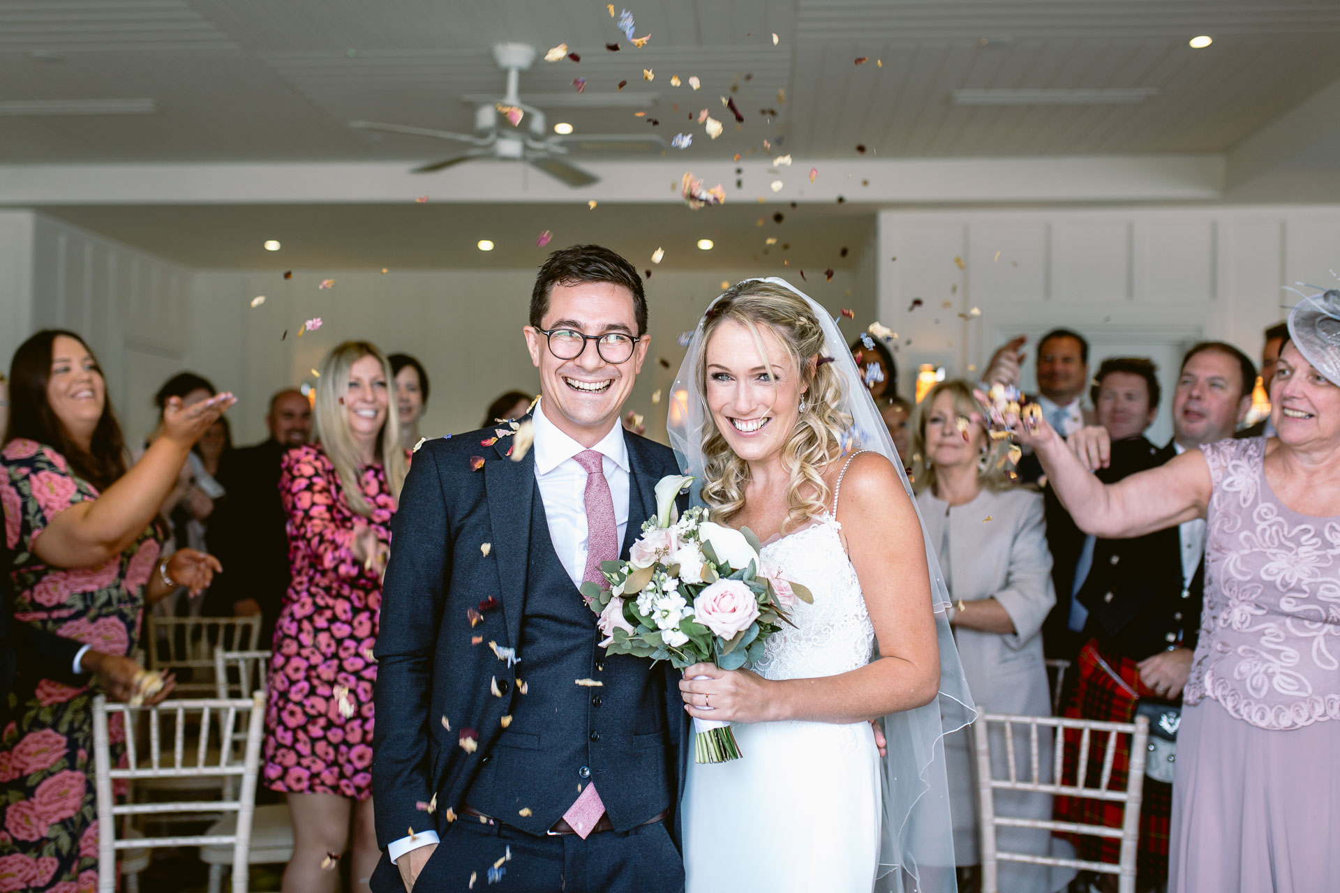 bride and groom standing at Salcombe Harbour Hotel and having confetti thrown upon them