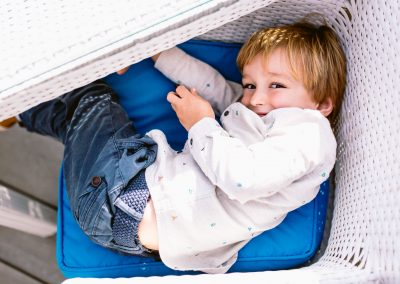 a little boy hiding in the chair in Salcombe hotel terrace wedding