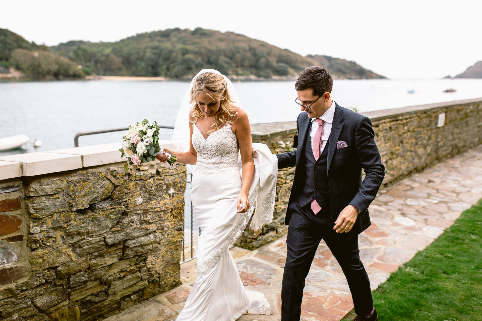 bride and groom walking down at a promenade in salcombe hotel wedding