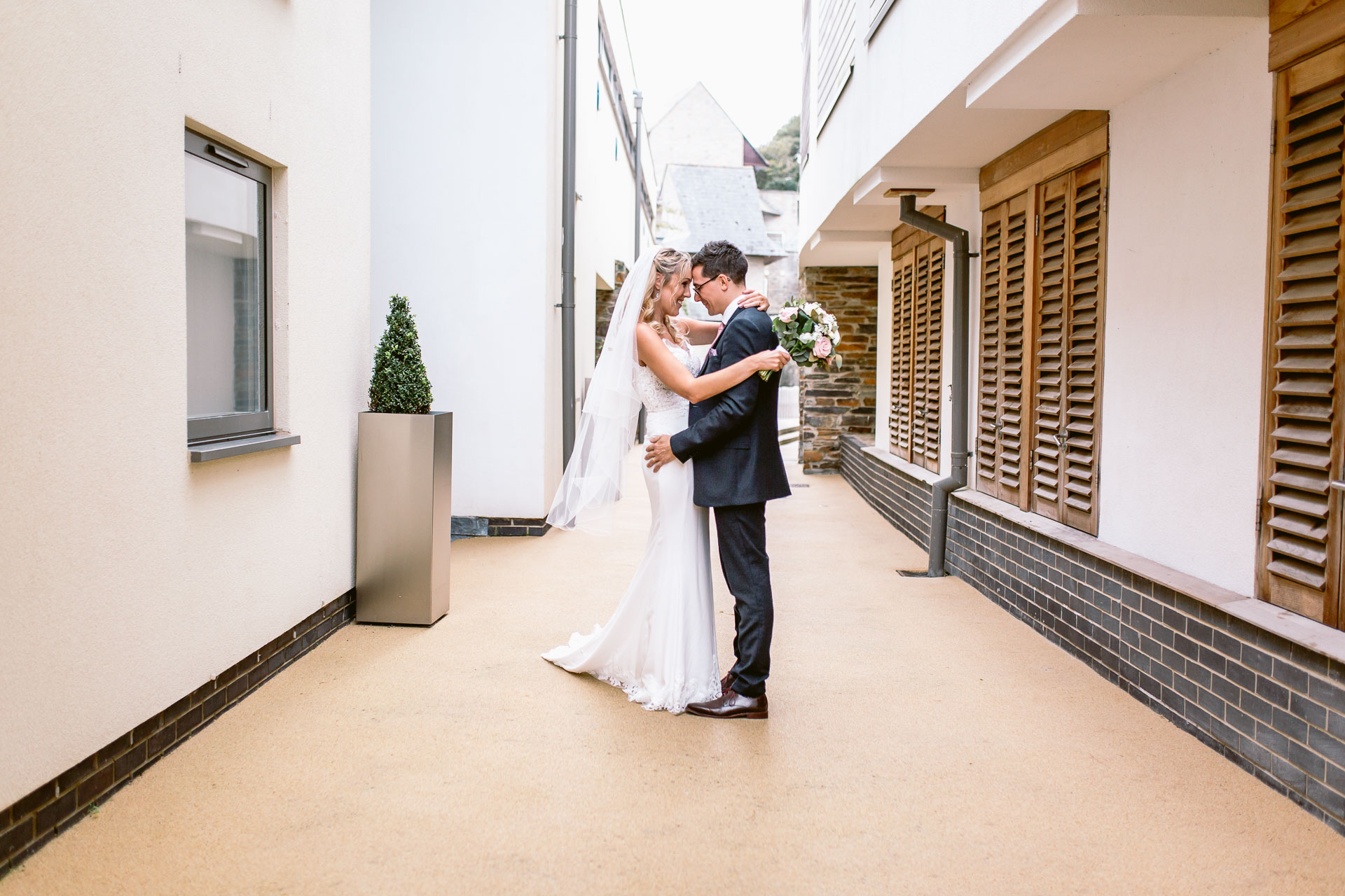 bride and groom standing close to each other and hugging in salcombe harbour hotel wedding