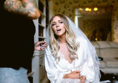 bride looking through the window while getting ready in Fonmon Castle summer wedding of Kelly and Jordan