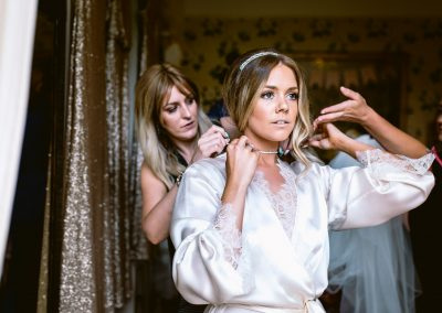 bride is putting her jewellery on and bridesmaids are helping in Fonmon Castle summer wedding of kelly and jordan