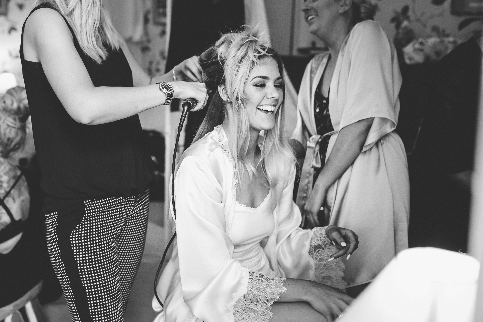 bride having her hair done and smiling sitting on the chair in Fonmon Castle