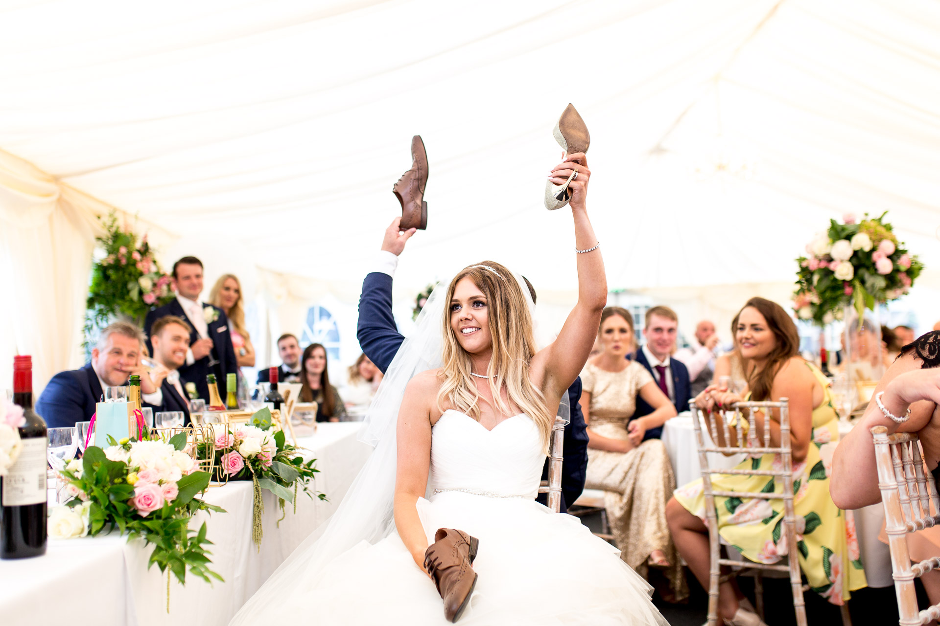 brode ang groom holding their shoes up during quiz at Fonmon Castle