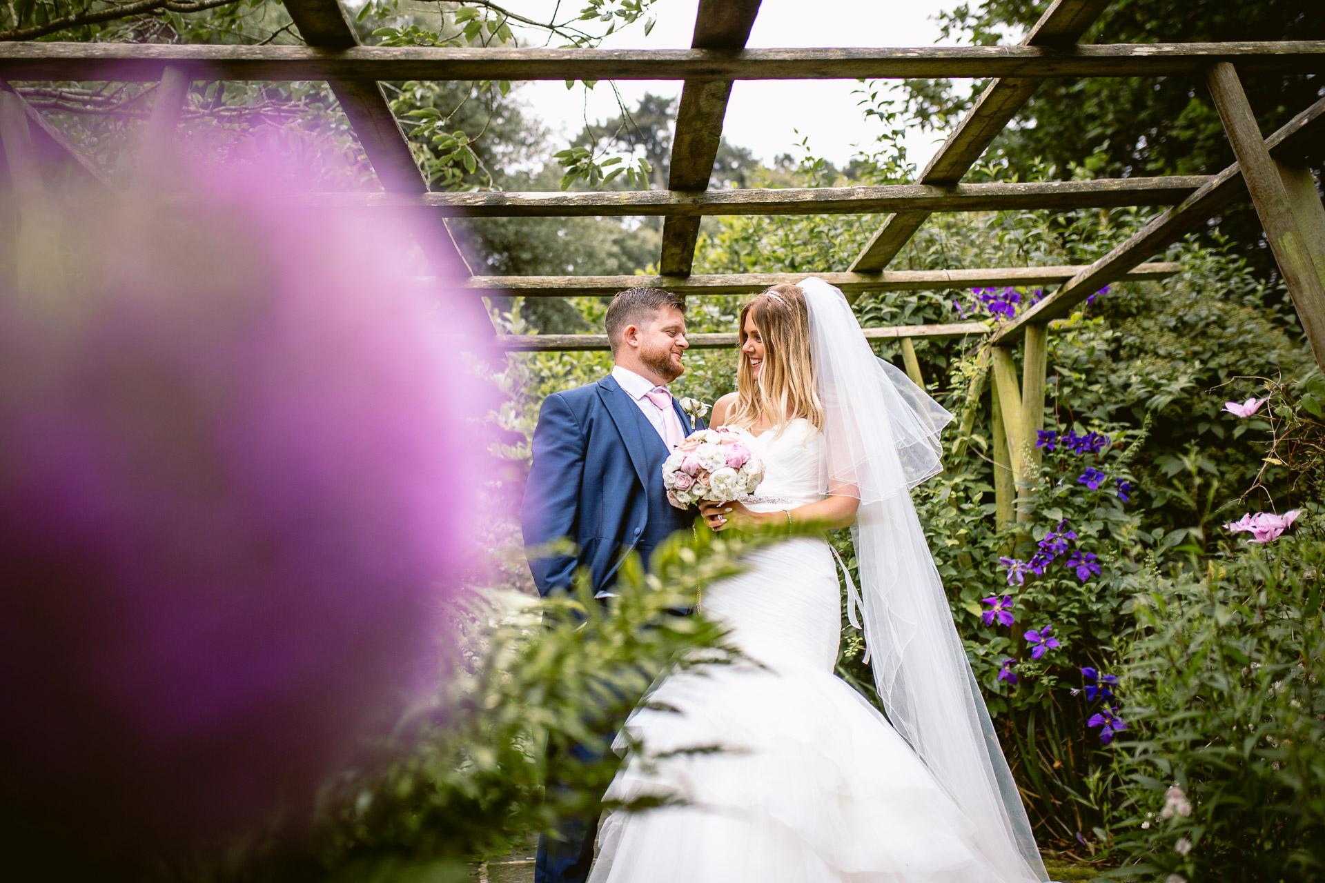 bride and groom standing among flowers in Fonmon Catsle
