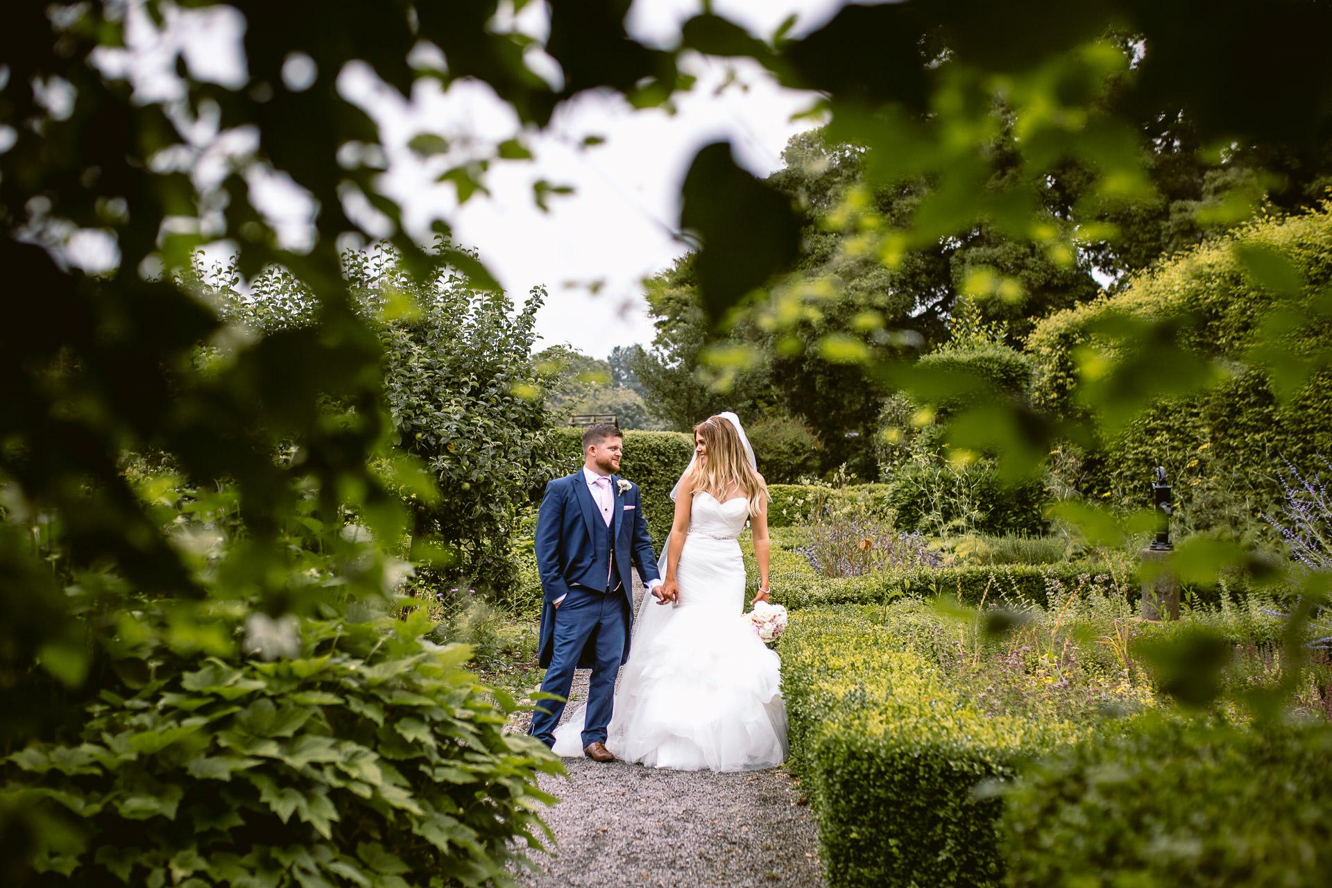 bride and groom standing in the gardens of Fonmon Castle