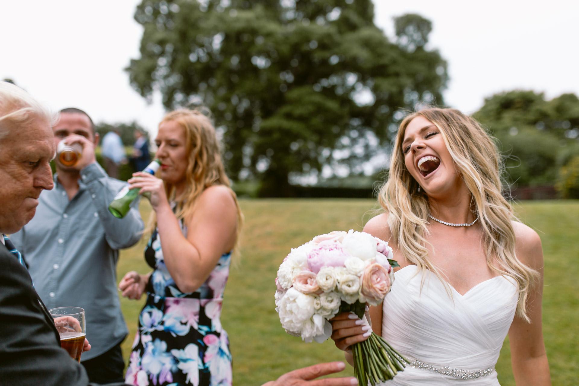 bride having a big laugh at her wedding in Fonmon Castle