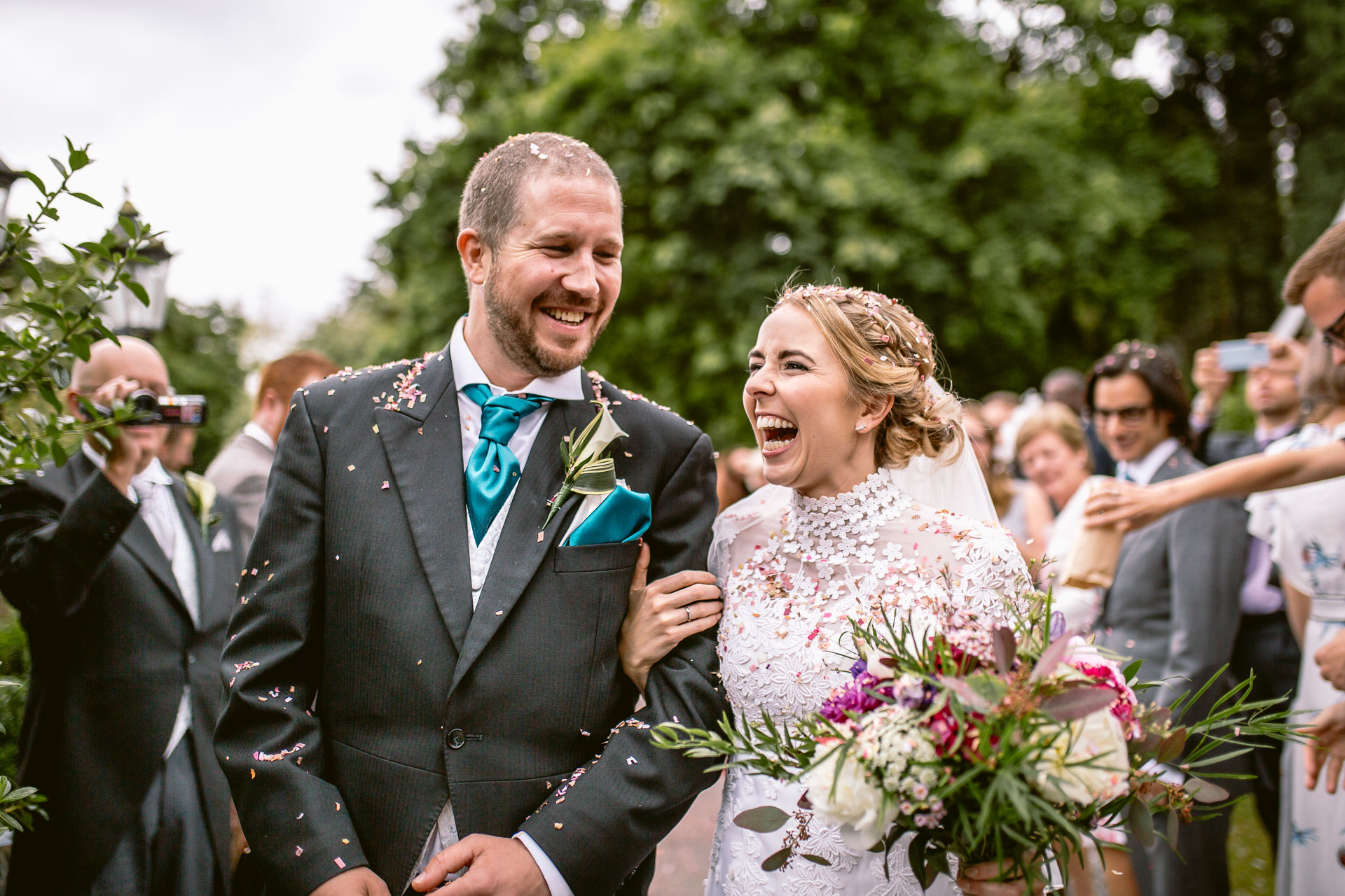 bride and groom laughing having confetti thrown over them in Pencoed House