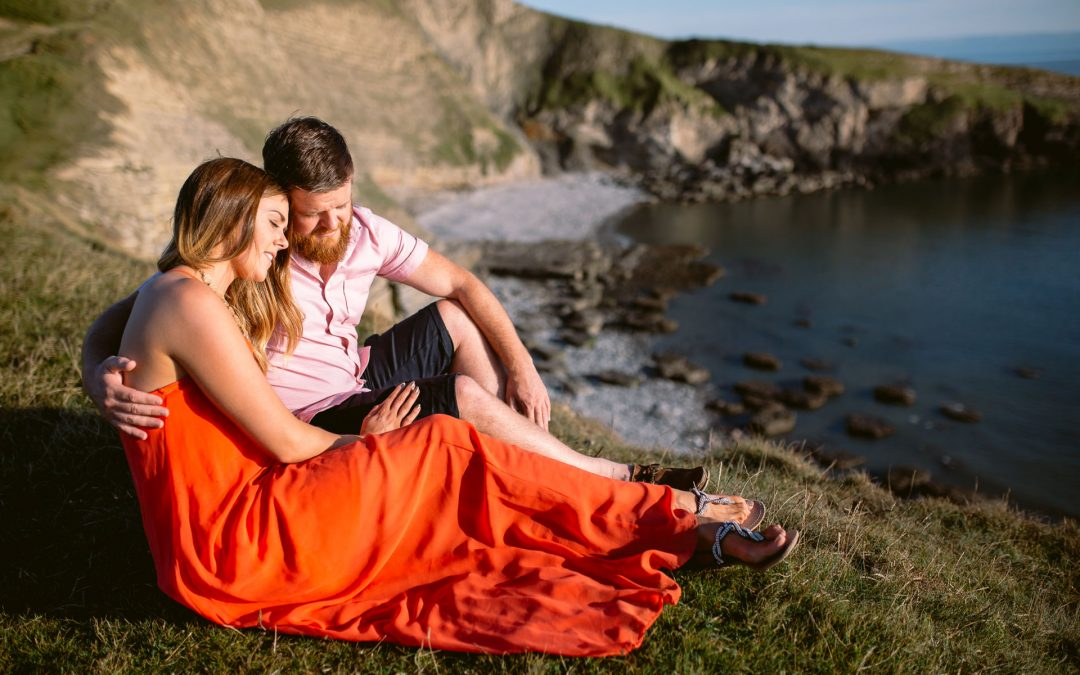 couple sitting on the edge of the cliff in a beautiful sunset during the beach sunset engagements session in Ogmore