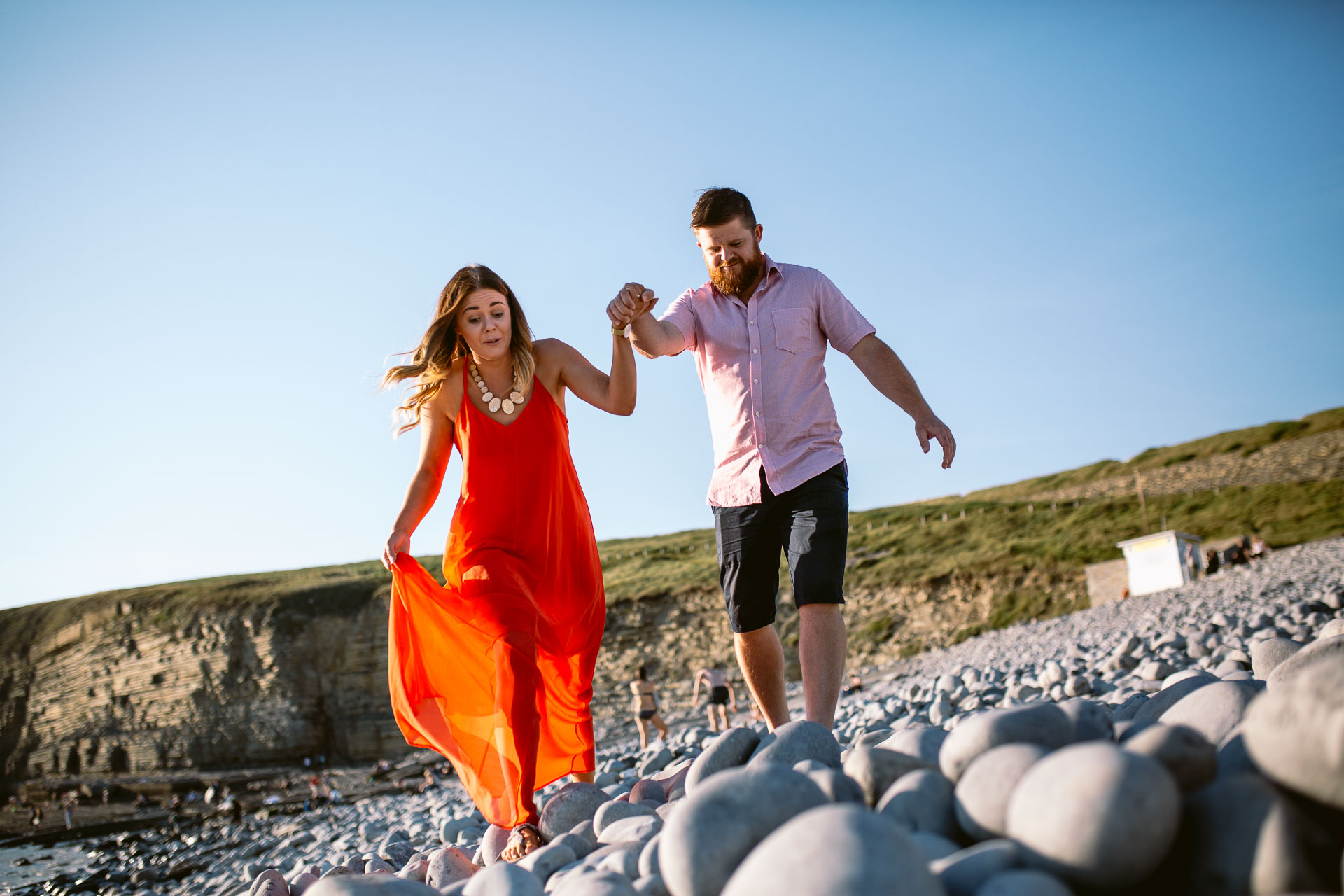couple is walking on the rocks on the beach sunset engagement session in Ogmore