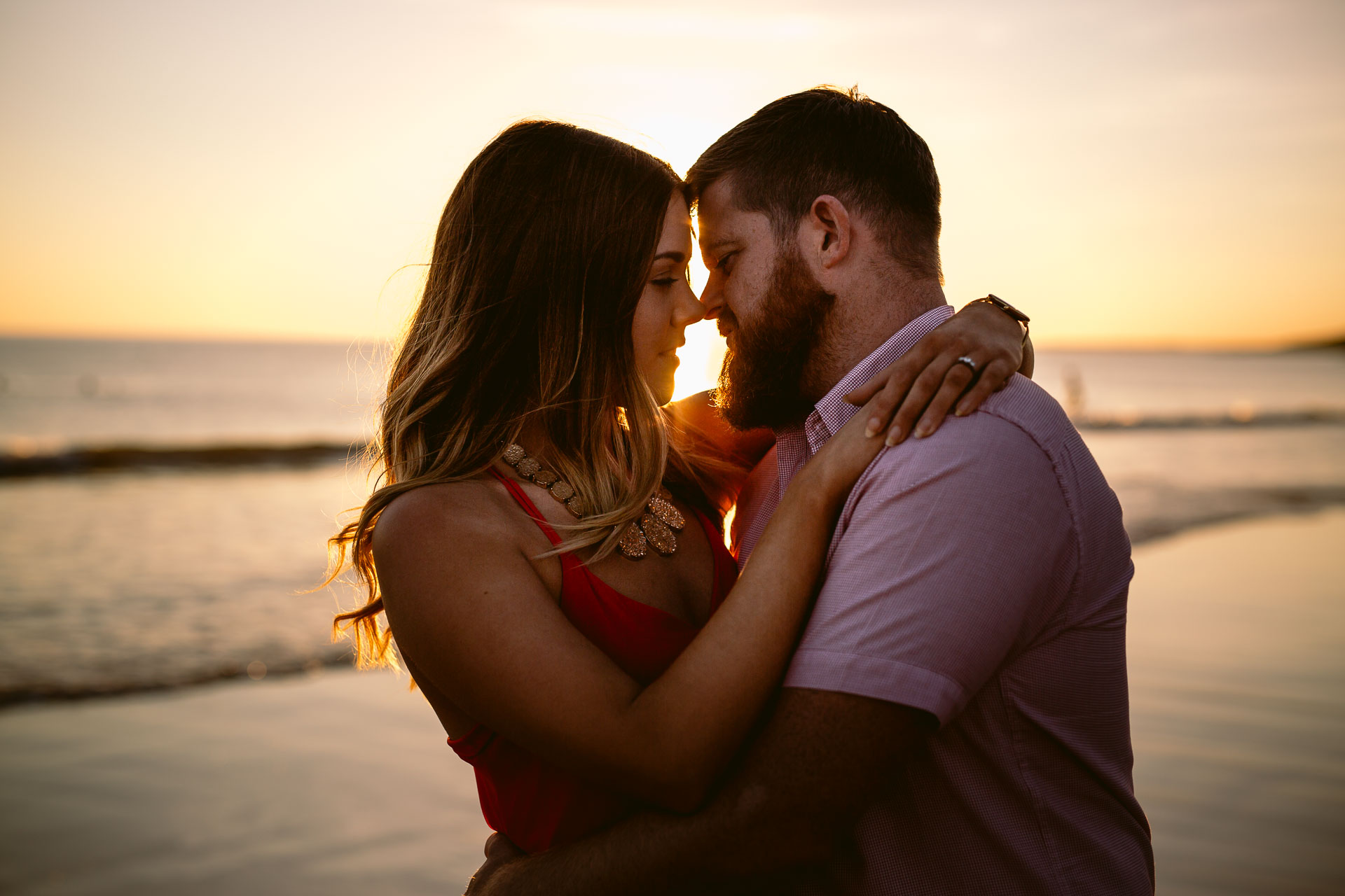 couple is hugging each other nose to nose during the beach sunset engagement session