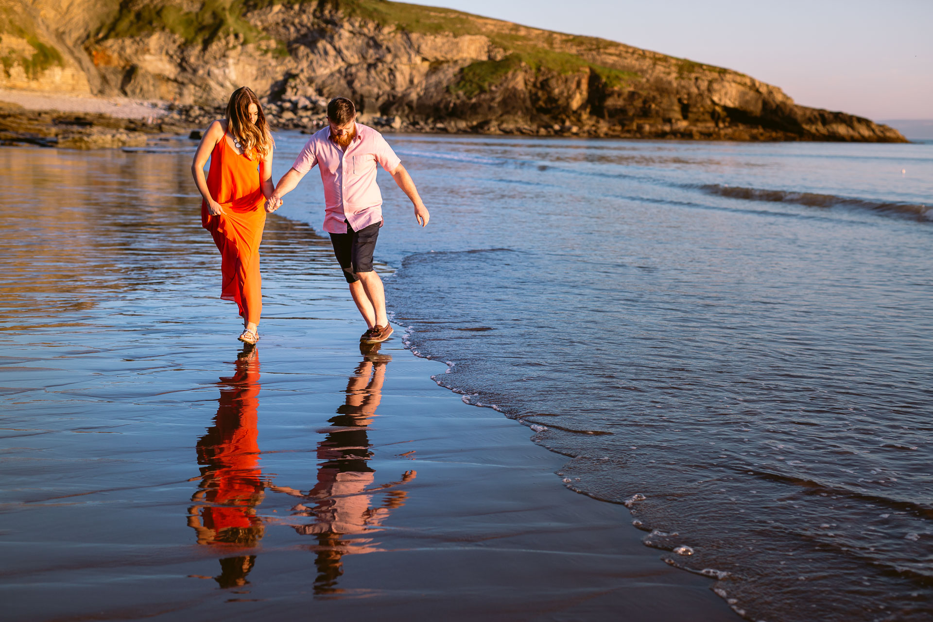 couple running off the waves on the beach walk in sun set during the beach sunset engagement session in Ogmore