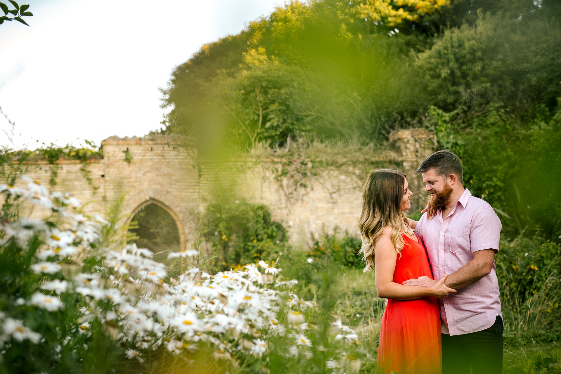 couple in love standing in the gardens and looking at each other during the beach sunset engagement session