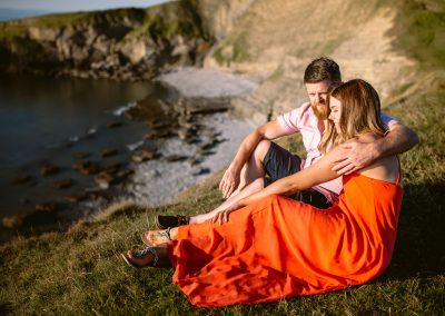 couple sitting on the edge of the cliff in the sunset during beach sunset engagement session