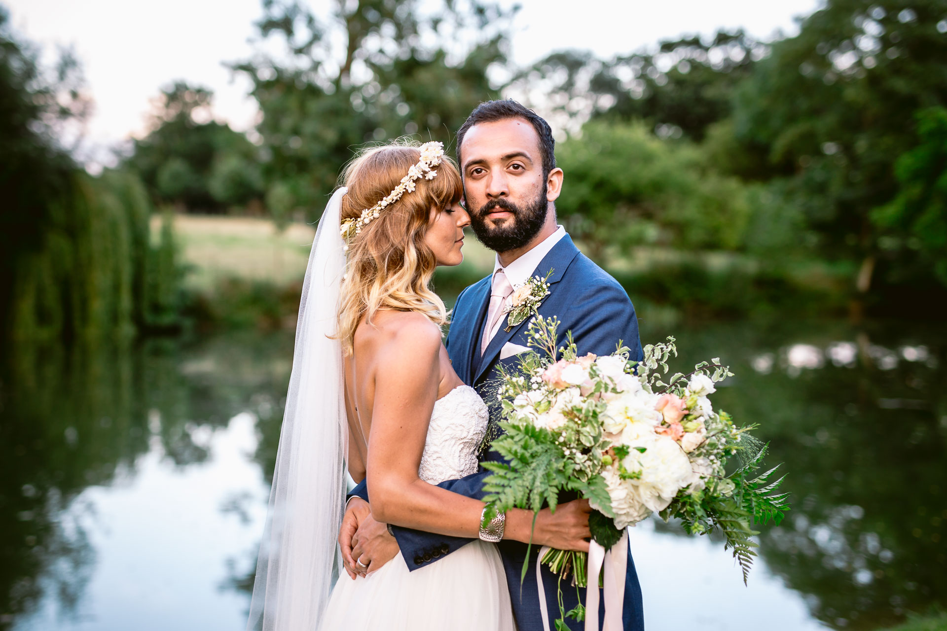 preston court boho wedding alexia and dan bride and groom standing by the lake with bouquet and hugging